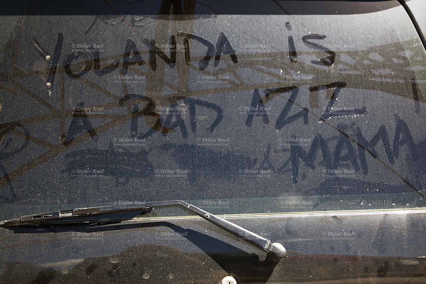 "Philippines. Province Eastern Samar. Hernani. A man wrote words on dirty rear window of a car: ""Yollanda is a bad ass, Mama"". 95 % of the town was destroyed by typhoon Haiyan's winds and storm surge. Typhoon Haiyan, known as Typhoon Yolanda in the Philippines, was an exceptionally powerful tropical cyclone that devastated the Philippines. Haiyan is also the strongest storm recorded at landfall in terms of wind speed. Typhoon Haiyan's casualties and destructions occured during a powerful storm surge, an offshore rise of water associated with a low pressure weather system. Storm surges are caused primarily by high winds pushing on the ocean's surface. The wind causes the water to pile up higher than the ordinary sea level. 25.11.13 © 2013 Didier Ruef"