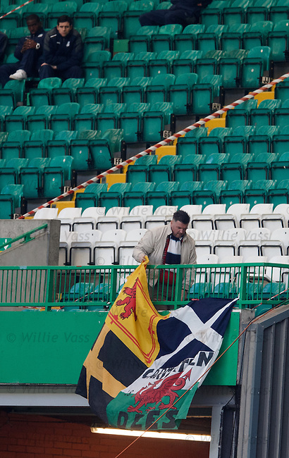 A Dundee fan takes his flags away before the end of the match