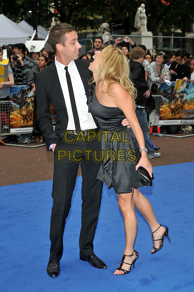 PHILIP TAYLOR & KATE WALSH.'Transformers: Revenge of the Fallen' .UK film premiere at Odeon cinema, Leicester Square, London, England..15th June 2009.full length black suit dress one shoulder couple hand in pocket phillip profile looking up down mouth open laughing funny .CAP/PL.©Phil Loftus/Capital Pictures