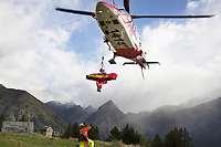 "Switzerland. Canton Ticino. Blenio valley. A Rega Agusta AW109 SP Grand ""Da Vinci"" helicopter lands on pastures above Olivone. By using a rescue hoist, a helicopter can rescue persons from hard-to-reach areas in the Alps. The emergency physician, Doctor Damiano Salmina, takes care of a badly injured man lying in a rescue bag. The patient is a worker from the Rotex company who was injured during a logging operation. All Rega helicopters carry a crew of three: a pilot, an emergency physician, and a paramedic who is also trained to assist the pilot for radio communication, navigation, terrain/object avoidance, and winch operations. The name Rega was created by combining letters from the name ""Swiss Air Rescue Guard"" as it was written in German (Schweizerische Rettungsflugwacht), French (Garde Aérienne Suisse de Sauvetage), and Italian (Guardia Aerea Svizzera di Soccorso). Rega is a private, non-profit air rescue service that provides emergency medical assistance in Switzerland. Rega mainly assists with mountain rescues, though it will also operate in other terrains when needed, most notably during life-threatening emergencies. As a non-profit foundation, Rega does not receive financial assistance from any government. People in distress can call for a helicopter rescue directly (phone number 1414). The AgustaWestland AW109 is a lightweight, twin-engine, helicopter built by the Italian manufacturer Leonardo S.p.A. (formerly AgustaWestland, Leonardo-Finmeccanica and Finmeccanica). Leonardo S.p.A is an Italian global high-tech company and one of the key players in aerospace. In close collaboration with the manufacturer, the Da Vinci has been specially designed to cater for Rega's particular requirements as regards carrying out operations in the mountains. It optimally fulfills the high demands made of it in terms of flying characteristics, emergency medical equipment and maintenance. Safety, performance and space have been increased, and maintenance and noise emissions red"