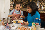 3 year old boy in kitchen at home with mother learning to cook baking, mixing ingredients in bowl