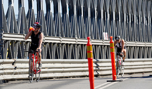 25 AUG 2013 - STOCKHOLM, SWE - Competitors cycle over a temporary bridge at the Gamla Stan end of the Söder Mälarstrand during the Stockholm Triathlon in Stockholm, Sweden (PHOTO COPYRIGHT © 2013 NIGEL FARROW, ALL RIGHTS RESERVED)