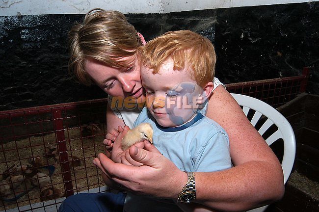 Rian Curley with his mam Gemma holding on of the newborn chicks at Newgrange farm..Photo: Colin Bell/Newsfile