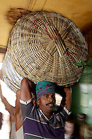Men carrying large baskets of food and good on their heads in the Kolay market in central Kolkata.<br /> <br /> To license this image, please contact the National Geographic Creative Collection:<br /> <br /> Image ID: 1925827 <br />  <br /> Email: natgeocreative@ngs.org<br /> <br /> Telephone: 202 857 7537 / Toll Free 800 434 2244<br /> <br /> National Geographic Creative<br /> 1145 17th St NW, Washington DC 20036