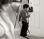 """Eric Llanos 5 of Cranbury, NJ, fidgety with therapy, hears the children outside playing on Saturday December 11 2005. """"Do you want to play outside with the children after your work is done Eric?"""", asks Eric's therapist Chasity Rivera a special education teacher from Union County.  """"I not want to, I can't."""" Ms. Rivera has been coming into the Llanos household teaching Eric verbal and fine motor skills since Eric was 18 months old. Chasity Rivera visits the Llanos family on Saturdays for 2 hours each week.The expenses for Eric's extra therapy comes out of the Llanos' pocket which means, Eric's father Riccardo works overtime to help alleviate the extra cost. Eric who is autistic, said his first word 6 months ago. Eric's mother Nancy, insisted that Eric's pediatrician refer Eric to a specialist when Eric was then only 1 year old. Nancy sensing something """"not right"""" with her son, was almost positive her son was autistic. Nancy also incurred problems with her insurance co. who could not figure out how to """"code"""" Eric. Eric and his family including father, mother, sister and grandparents are all part of a CDC genetic research study conducted by UMDNJ. photo by jane therese"""