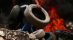 A Palestinian protester burns tires during clashes with Israeli troops following a demonstration against the expropriation of Palestinian land by Israel in the village of Kfar Qaddum, near Nablus, in the occupied West Bank on June 29, 2018. Photo by Shadi Jarar'ah