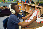 Black seven year old male in second grade classroom sits at auditory table listening to story with headphones and following the page.