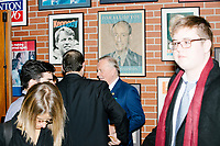 People gather in a lobby surrounded by previous decade's political campaign posters after Vice President Mike Pence spoke at a Politics and Eggs event at Saint Anselm College's Institute of Politics in Manchester, New Hampshire, on Thu., November 7, 2019. Pence traveled to New Hampshire as a surrogate for Donald Trump to file required paperwork for the president to get on the New Hampshire presidential primary ballot in 2020.