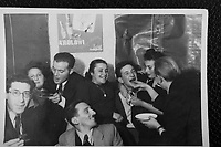 [wedding reception?] party.  [maybe] Simon's Sister - second from left.  Henryk Ross - seated in front.  Mendel Grossman - third from right - being forced to eat cake.