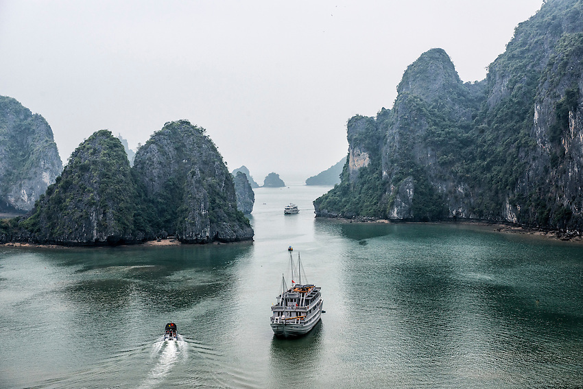"A view of Ha Long Bay from the mouth of a cave located 300 steps above the sea.  Ha Long Bay, located on the east coast of Vietnam near Haiphong, contains over 1,900 limestone ""karst"" islands projecting from the sea."