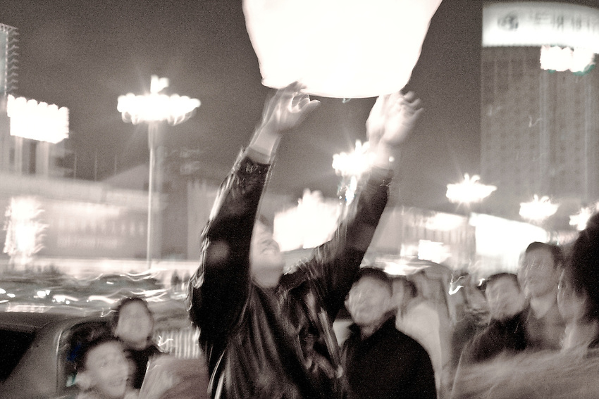 A man is lighting a paper lantern during the Lantern Festival in  Lanzhou (Gansu province). February 9 2009.