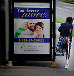 "August 22, 2013  copyright JimMendenhallPhotos.com 2013 jim mendenhall  sign at bus stop reads, ""You Deserve Better,"" as an ad for health care while the image of a happy white family smiles into the camera. Meanwhile, a black man with one arm and one leg happens past on Blvd. of the Allies, in Pittsburgh, Pa"