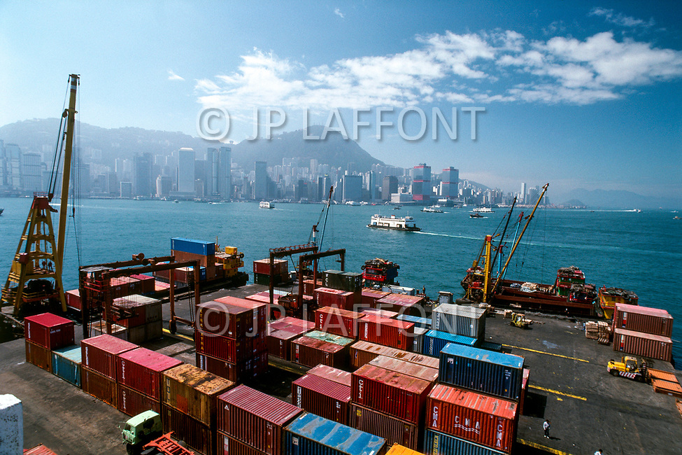 1988, Hong Kong, China --- Shipping containers are unloaded on the dockside at a port in Hong Kong. --- Image by © JP Laffont