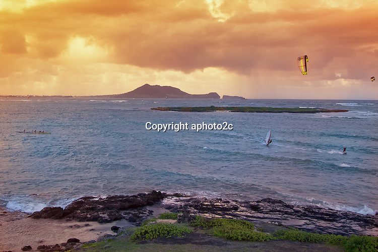 Kailua bay on a windy late afternoon draws many ocean sport activities. Kite surfing, wind surfing, canoe paddling and surfing.