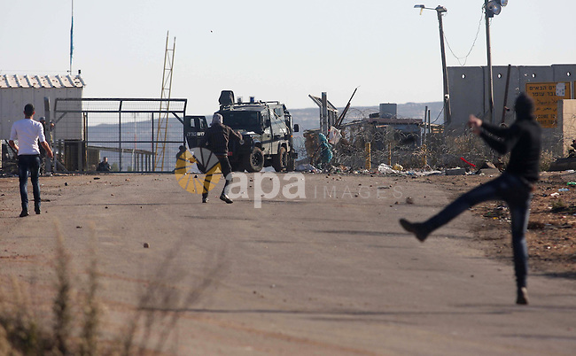 Palestinian protesters throw stones at Israeli troops during clashes against Israel's operations in Gaza Strip, outside Ofer, an Israeli military prison near the West Bank city of Ramallah, Thursday, Nov. 15, 2012. Meanwhile, Palestinian President Mahmoud Abbas cut short a trip to Europe to deal with the crisis. Photo by Issam Rimawi