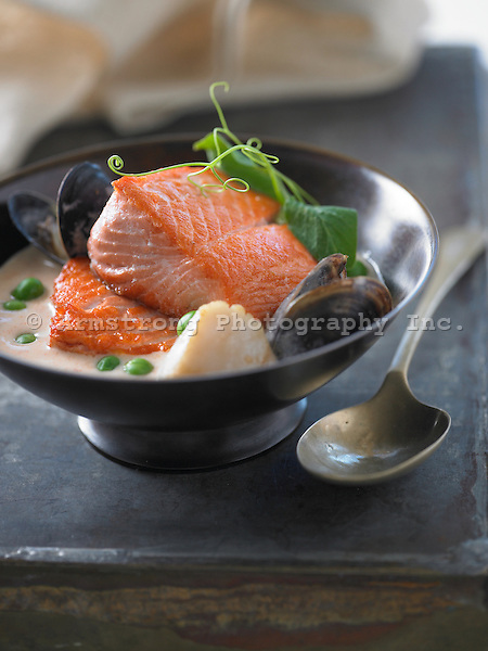 Large pieces of salmon in seafood broth, with mussels, scallops, peas, and pea shoots.