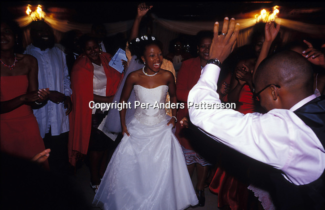 dipewed0011 People Wedding MULDERSDRIFT, SOUTH AFRICA - APRIL 19: Yolissa Koza, a consultant for an international management consulting company, dances with her relatives and friends during the reception after her wedding on April 19, 2003 Makiti, an exclusive lodge in Muldersdrift outside Johannesburg, SA. Yolissa and her husband Sandile belong to the new black elite in the country. The couple, educated and connected, has successful careers and belongs to growing number of black elite that has money to spend on luxury items and western influenced lifestyle. They invited about five hundred guest to the exclusive western styled wedding. Yolissa arrived in a helicopter with her parents. .Photo: Per-Anders Pettersson/iAfrika Photos....
