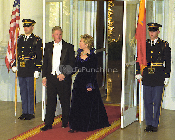 United States President Bill Clinton, left, and first lady Hillary Rodham Clinton, right, hold hands as they exit the door to the North Portico of the White House in Washington, D.C. to await the arrival of King Juan Carlos I and Queen Sofia of Spain for a State Dinner on February 23, 2000.<br /> Credit: Ron Sachs / CNP/MediaPunch