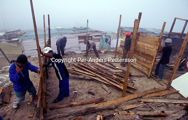 diinhu00106 Construction. Men building a shack for a family on August 8, 2001 in the Site B section in Khayelitsha, a township about 35 kilometers outside Cape Town, South Africa. Most people live in these shacks that can be bought at several places in the township. Khayelitsha is one of the poorest and fastest growing townships in South Africa. People usually come from the rural areas in Eastern Cape province to find work as maids and laborers. Most people don't find work and the unemployment rate is very high, together with lot of violence and a growing HIV-Aids epidemic itÕs a harsh area to live in. Housing.©Per-Anders Pettersson/iAfrika Photos..