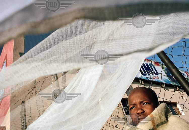 A child stands beneath curtains by the village store in Intabazwe township in Harrismith.