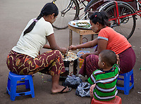 Myanmar, Burma, Yangon.  Two Women Cooking Food to Sell to Passersby.  They have light coatings of thanaka paste on their faces, as a cosmetic sunscreen.