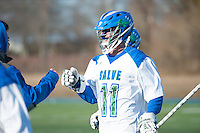 Steven Russell,'15, is congratulated by teammates as the Salve Regina men's lacrosse team dominates Anna Maria at Gaudet Field in Middletown.