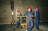 Switzerland. Canton Lucerne. Three bored men with red helmets and a mobile traffic light in the Sonnenberg tunnel in Lucerne during the largest civil defense exercise ever held in the country. From 16 to 21 November 1987, almost 1200 men and women converted a motorway tunnel into perhaps the world's largest bunker structure. The civil protectors had to prove during the exercise «Ameise» ( Ants in english) that in an emergency more than 20,000 inhabitants of the city of Lucerne could survive here in the mountain for two weeks. The Sonnenberg Tunnel is a 1,550m  long motorway tunnel, constructed between 1971 and 1976. At its completion it was also the world's largest civilian nuclear fallout shelter, designed to protect 20,000 civilians in the eventuality of war or disaster. Based on a federal law from 1963, Switzerland aims to provide nuclear fallout shelters for the entire population of the country. The construction of a new tunnel near an urban centre was seen as an opportunity to provide shelter space for a large number of people at the same time. The giant bunker was built between 1970 and 1976 at a cost of 40 million Swiss francs. The shelter consisted of the two motorway tunnels (one per direction of travel), each capable of holding 10,000 people in 64 person subdivisions. A seven story cavern between the tunnels contained shelter infrastructure including a command post, an emergency hospital, a radio studio, a telephone centre, prison cells and ventilation machines. The shelter was designed to withstand the blast from a 1 megaton nuclear explosion 1 kilometer away. The blast doors at the tunnel portals are 1.5 meters thick and weigh 350 tons. The logistical problems of maintaining a population of 20,000 in close confines were not thoroughly explored, and testing the installation was difficult because it required closing the motorway and rerouting the usual traffic. The only large-scale test, a five-day exercise in 1987 to practice converting the road tun