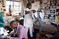 SOWETO, SOUTH AFRICA JULY 3: Sibu Sithole (c), a young designer part of the group Smarteez work on a collection with his colleague Lethabo Tsatsinyane in their workshop on July 3, 2014 in Jabulani section of Soweto, South Africa. Soweto today is a mix of old housing and newly constructed townhouses. A new hungry black middle-class is growing steadily. Many residents work in Johannesburg but the last years many shopping malls have been built, and people are starting to spend their money in Soweto. (Photo by: Per-Anders Pettersson)