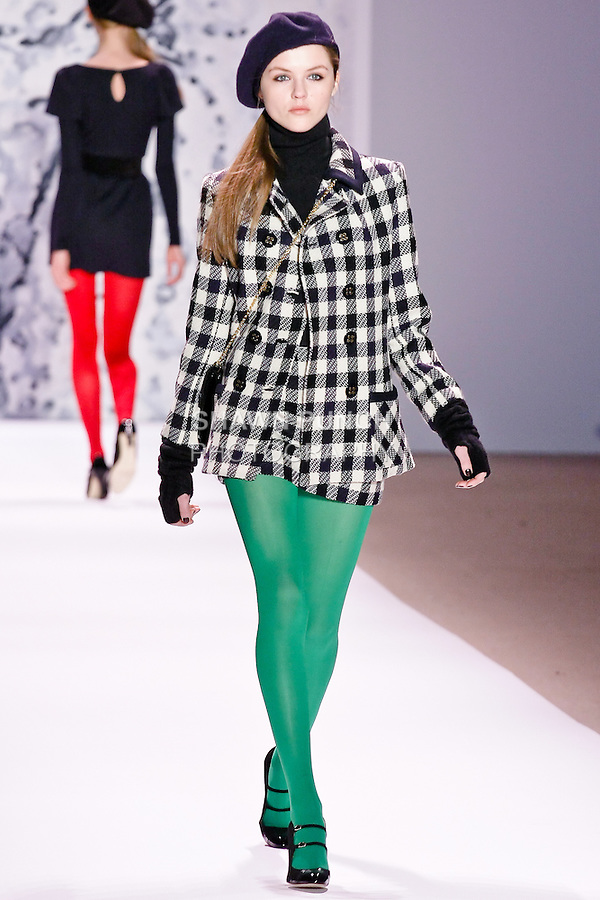 """Rasa Zukauskaite walks runway in a navy check wool piped peacoat, black cashmere turtleneck sweater, and navy check wool mini skirt, by Michelle Smith for her Milly Fall Winter 2010 """"Classique=Moderne"""" collection, during the Mercedes-Benz Fashion Week Fall 2010."""