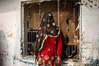 A woman belonging to the Babaria caste stands next to a delapidated building in Panipat. The Babaria are a major source of illegally traded tiger parts since they used to hunt them when it was legal to do so and now sell them to traffickers.