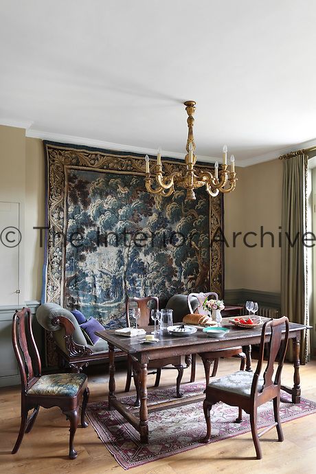 A cream dining room furnished with antique chairs and table, with a faded French tapestry hanging over green wainscoting