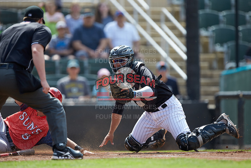 Kannapolis Intimidators catcher Carlos Perez (8) looks at home plate umpire Forrest Ladd for a call as Cole Freeman (8) of the Hagerstown Suns slides across home plate at Kannapolis Intimidators Stadium on May 6, 2018 in Kannapolis, North Carolina. The Intimidators defeated the Suns 4-3. (Brian Westerholt/Four Seam Images)