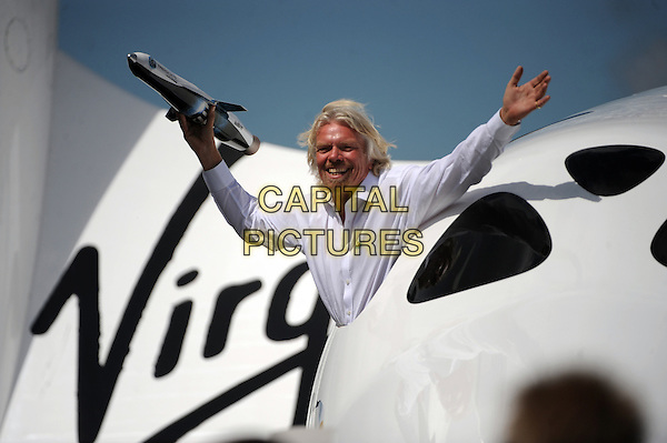 Sir Richard Branson .appearing this morning at the Farnborough Airshow 2012. The entrepreneur announced he would be travelling to space on SpaceShipTwo with his children Holly and Sam..Farnborough, England 11th July 2012.*Editorial Use Only*.half length white shirt arms hands in air  model  goatee facial hair .CAP/PLF.© Farnborough Airshow/Capital Pictures.