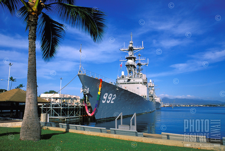 "A  U.S  Naval vessel returns to Pearl Harbor with a ceremonial hawaiian lei  draped over its bow.  A way of saying """"Welcome Home"""" to Hawaii."