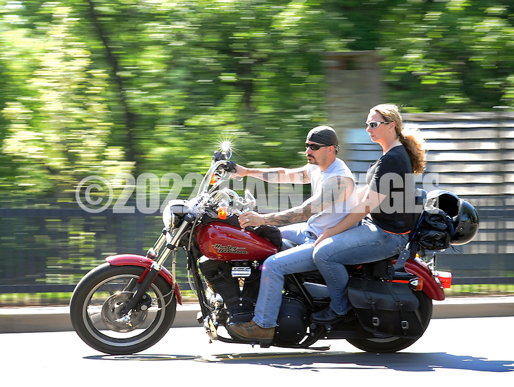 NEW HOPE, PA - JUNE 02:  An unidentified couple rides a motorcycle on Main Street on a warm afternoon June 2, 2014 in New Hope, Pennsylvania.  The temperature reached 82 degrees in New Hope and is expected to remain in the mid-80's for the next few days. (Photo by William Thomas Cain/Cain Images)