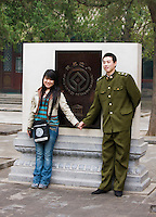 Young couple pose holding hands for a photograph at The Summer Palace, Beijing, China