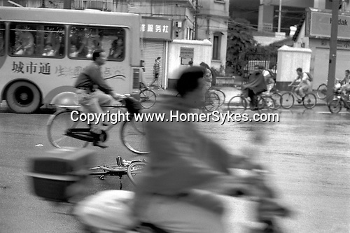 China, Shanghai. Evening commuters hurry to get home one rainy evening. Although normally the leader in transport revolutions, where bicycles are concerned Shanghai lost out to Tianjin, the location of China?s first bicycle shop in 1915. Bicycles could not be purchased in Shanghai until 1932 when imported parts were assembled for the affluent few.  In 1940 the Shanghai Forever Bicycle Company went into production and there are now over three million cyclists in Shanghai...