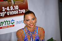 "Melitina Staniouta of Belarus smiles to camera at ""kiss & cry"" during event finals at 2010 Holon Grand Prix at Holon, Israel on September 4, 2010.  (Photo by Tom Theobald)."