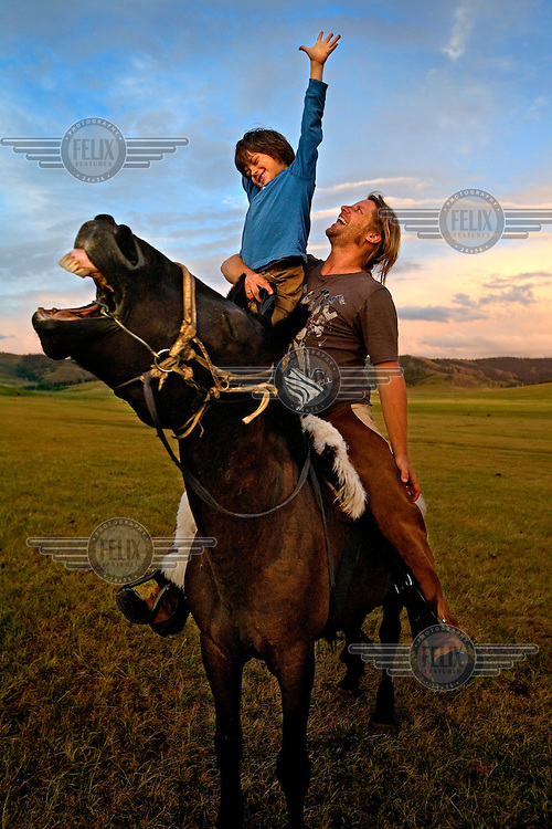 """Rupert Issacson, a campaigning writer and former horse trainer, sits with his five-year-old autistic son, Rowan, on a horse during an expedition across Mongolia. Rowan, who has been nicknamed """"The Horse Boy"""", embarked on a therapeutic journey of discovery with his parents to visit a succession of shaman healers in one of the most remote regions in the world. Following Rowan's positive response to a neighbour's horse, Betsy, and some reaction to treatment by healers, Rowan's parents hoped that the Mongolian shamanistic rituals along the route and the prolonged contact with horses would help to unlock their son's autism and assist his development.."""