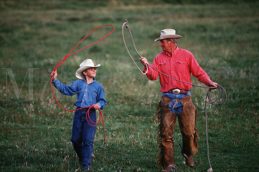 A cowboy teaches roping to a young boy.