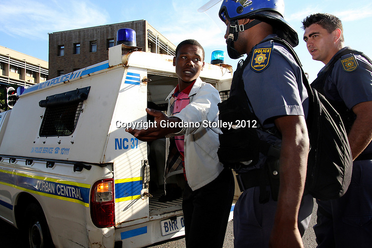 DURBAN - 18 May 2012 - A protesting taxi driver remonstrates with a police officer after being ordered into the back of a police van with fellow drivers. The taxi drivers were demanding the release of their compatriots, who were arrested on Thursday during protests against the eThekwini Metro police..Picture: Giordano Stolley/Allied Picture Press/APP