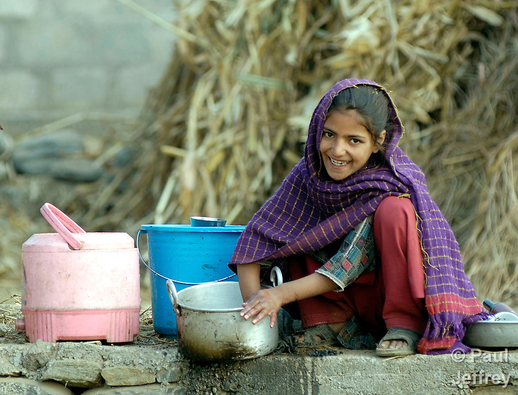 Following an October 8, 2005, earthquake, a girl washes dishes in a tent city outside Balakot sponsored by Church World Service/Action by Churches Together.