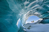 Two cross country skiers peer into a glacier ice cave formed by the melting water under the glacier in the Alaska Range mountains.