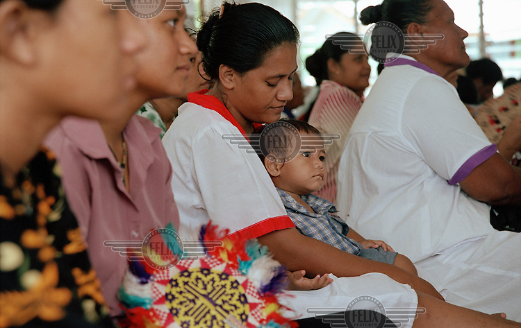 A mother and her child sit among the female members of the congregation at the Church of Tuvalu, known as Ekalesia Kelsiano Tuvalu. ...
