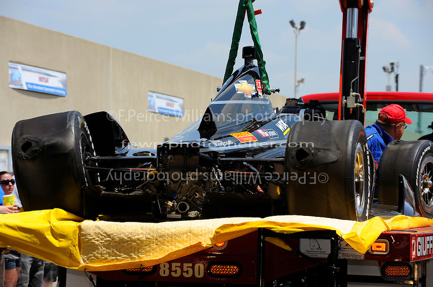 The crashed car of Oriol Servia (#22) is brought back to the pits.