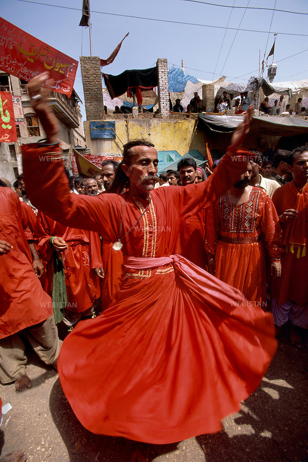 SEHWAN SHARIF, PAKISTAN - SEPTEMBER, 2006:  Whirling dervishes (Malangs) during the annual celebration of the Urs of Lal shahbaz Qalandar, a 13th century Sufi Master worshiped alike by Hindus and Muslims. Born as Seyed Shah Hussain (Usman) Marandi, he later on titled as Lal (red) Shahbaz ( Falcon) Qalandar (as he belonged to Qalandria order of sufism)..By whiriling, the dervishes perfom Dhmal, an ecstatic dance through which they aim to purify their souls and reach perfectness. Different sect of religion brings different ways of clothing. These followers wear red clothes as Lal Shahbaz Qalandar was wearing red all his life.