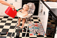 A child in high chair suckles a gas can in a kitchen.