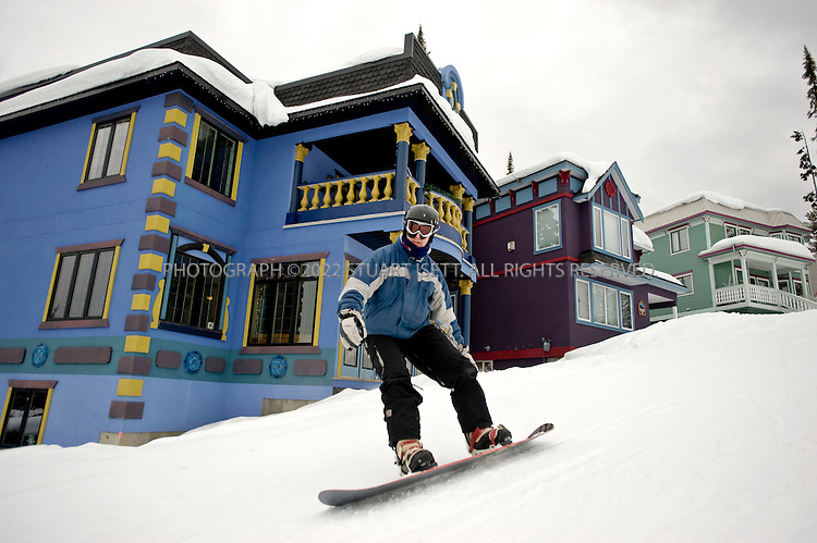 3/12/2008--SIlver Star Mountain, British Columbia, Canada..Robert Wineck, from Ottawa, Canada, sknow boards past large homes for rent and sale at the Silver Star Mountain Resort. Silver Star Mountain Resort, British Columbia with most of its buildings designed in the Victorian Era style. The mile-high resort is surrounded by British Columbia provincial park lands and its small pedestrian-only village nestles mid-mountain. Silver Star Mountain lies in the interior of British Columbia amidst mountain ranges, valleys and lakes..In winter, the mountain resort offers 115 ski and snowboard trails including thirteen double black diamond runs for the more adventurous or teenaged members of the family. The summer hosts a smaller crowd, with activities for the mountain biker, nature lover, and golf is nearby...In the last six years, Silver Star has begun to transform from sleepy provincial ski area to world class boutique family resort. In 2002, the Schumann family bought the resort, and have invested $25M in five new chair lifts and other infrastructure. Now, builders are using higher quality fit and finish on new luxury condominium complexes, home prices are going up, and some winter weekends are selling out...©2008 Stuart Isett. All rights reserved