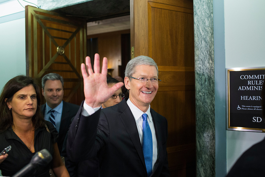 Apple CEO Tim Cook waves as he departs after testifying at a Senate homeland security and governmental affairs investigations subcommittee hearing on offshore profit shifting and the U.S. tax code, on Capitol Hill in Washington. Cook  defended the company's tax record during a Senate hearing where lawmakers said the maker of iPads, iPods and Mac computers kept billions of dollars in profits in Irish subsidiaries to avoid U.S. taxes.