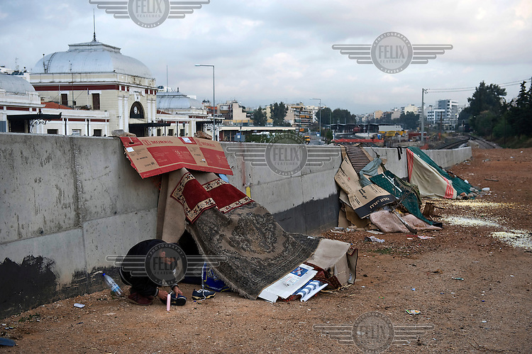 An Algerian illegal immigrant polishes his trainers in front of his carton box shack, near Larissis railway station in the centre of Athens. According to UNHCR, 38,992 immigrants arrived in Greece in the first 10 months of 2010, whereas in 2009 the number was only 7,574.